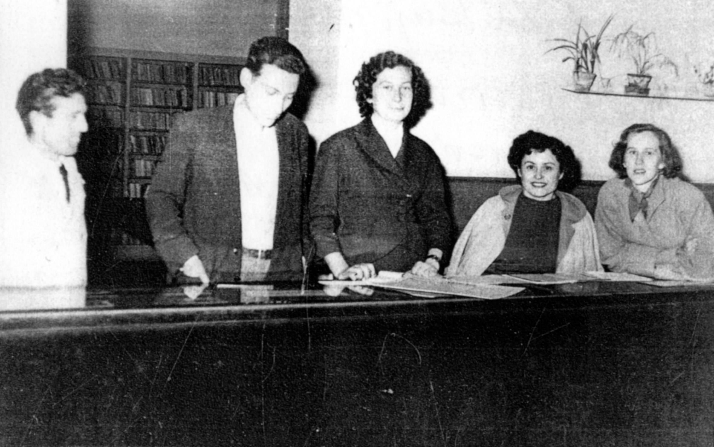 Za pultom Gradske knjižnice Zadar 1956: djelatnici Znanstvene knjižnice Pavao Galić i Danica Maršan. Desno su Ivka Karavida iz Gradske knjižnice i supruga Ante Ivića, prvoga djelatnika Gradske knjižnice Zadar